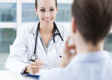 læge taler med kvinde i behandling
