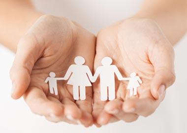 Hænder holder børnefamilie i papir