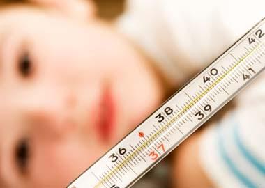 Barn med feber og thermometer