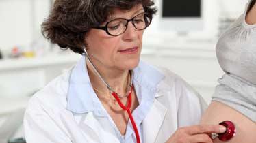 læge lytter til gravid mave