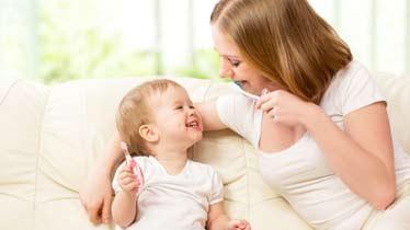 mor og barn sidder i sofa og børster tænder