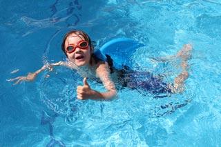 Barn svømmer giver thumbsup