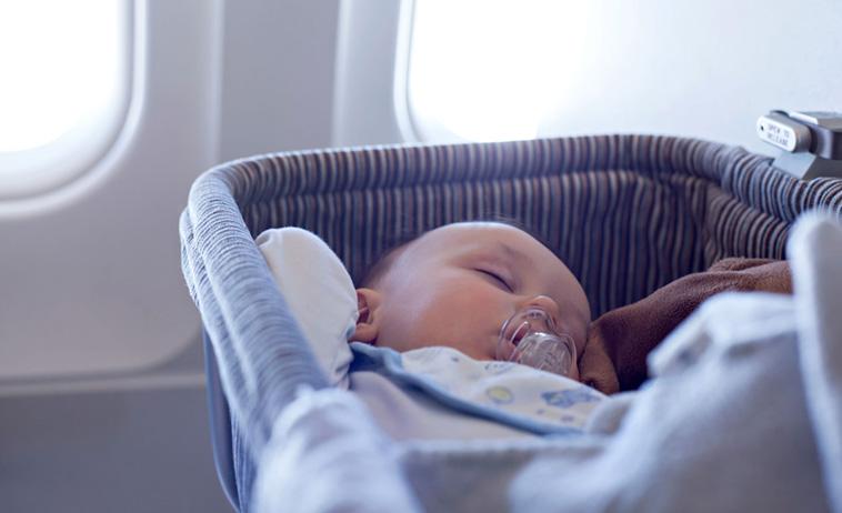 baby sover i vugge i fly