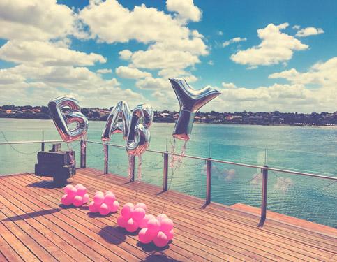 træterasse ved vandet pyntet med bogstav balloner