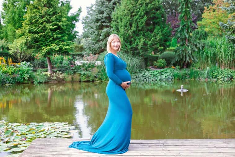 gravid kvinde i blå kjole ved sø