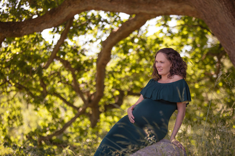 gravid kvinde i blå kjole i skov