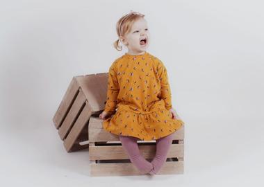 Pige sidder på trækasse