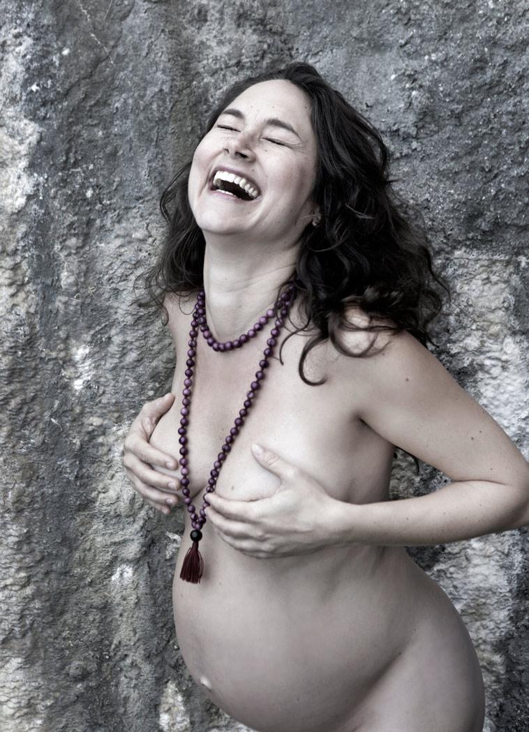 gravid kvinde griner og dækker sine bryster