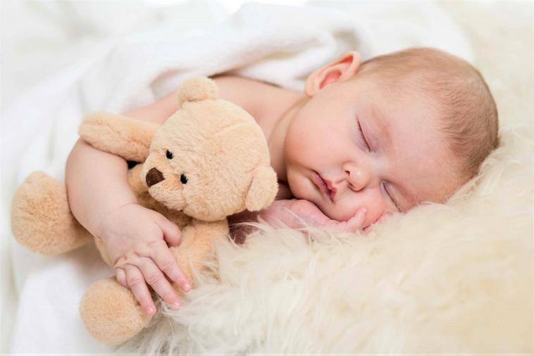 sovende baby med en bamse